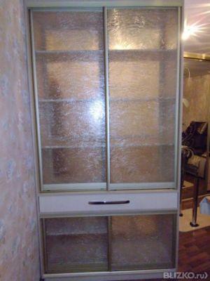 Шкаф-витрина с распашными створками из полупрозрачного стекл.